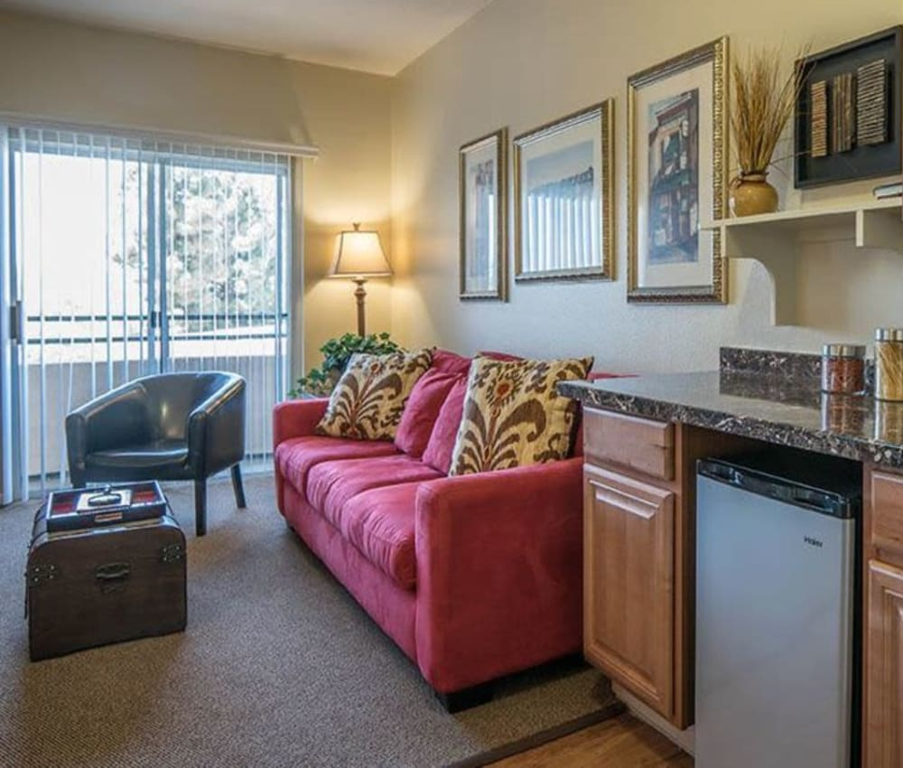Spacious living room next to the kitchen in one of our independent living suites at Carmel Village in Fountain Valley, California