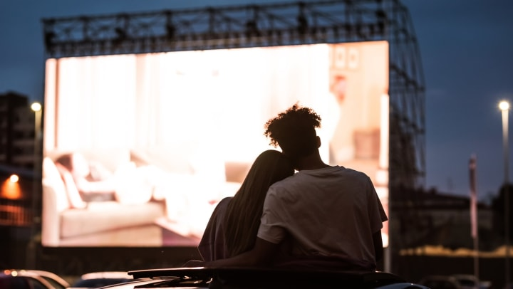 Silhouetted view of a couple embracing while watching a movie in a drive-in.
