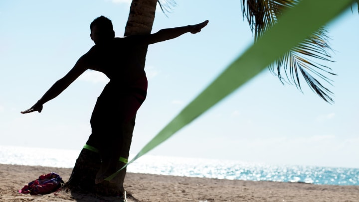 Resident slacklining between palm trees at the beach near The Hawthorne in Jacksonville, Florida