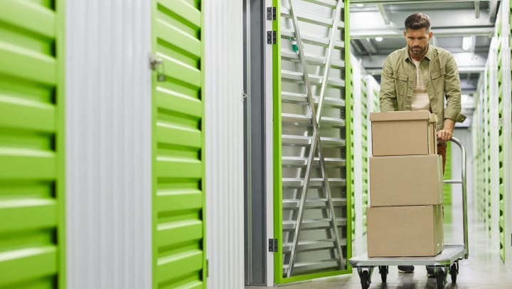 Man pushing a loading cart with boxes stacked on it into a self storage unit