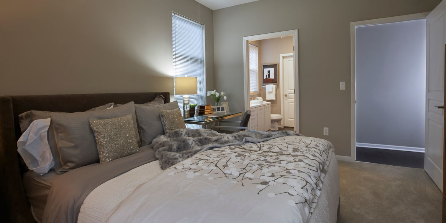 Bedroom with plush carpeting and an en suite bathroom in a model home at Uptown Ann Arbor in Ann Arbor, Michigan