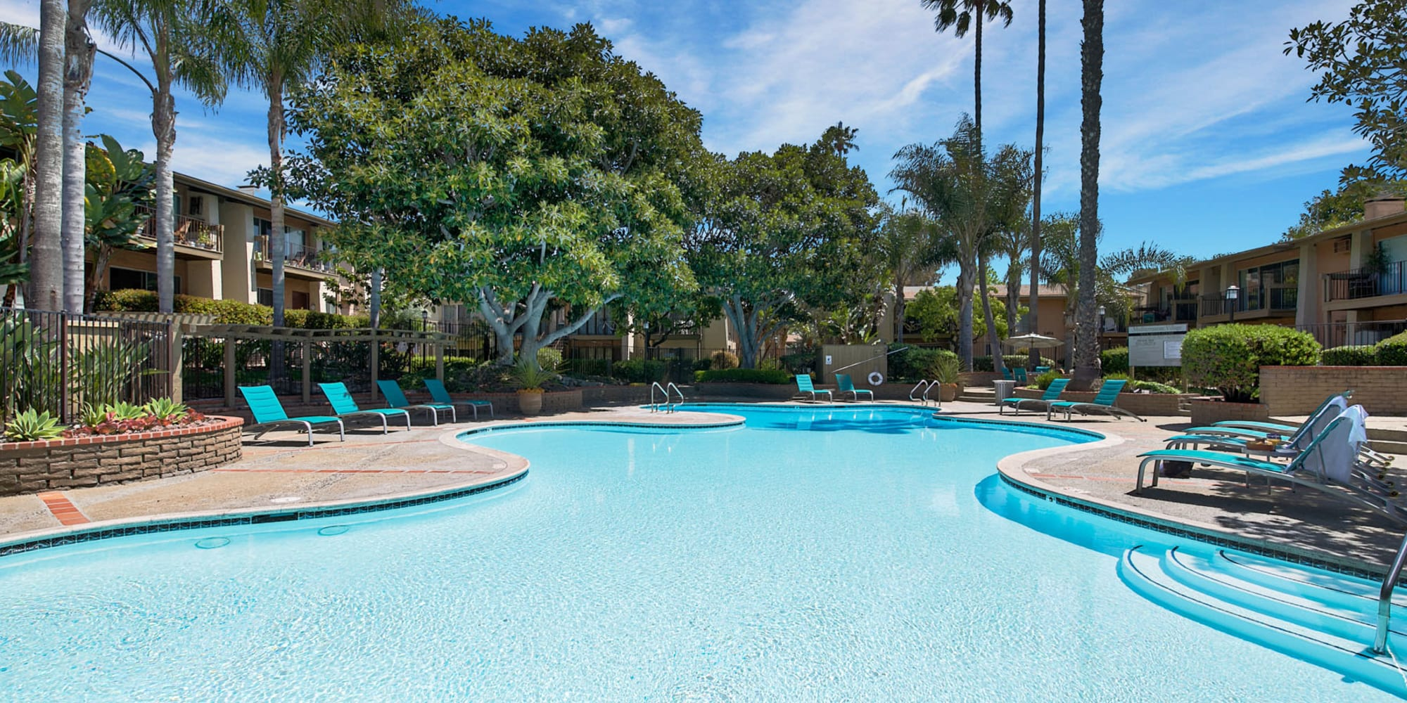 Resort-style swimming pool on a beautiful day at Mediterranean Village Apartments in Costa Mesa, California