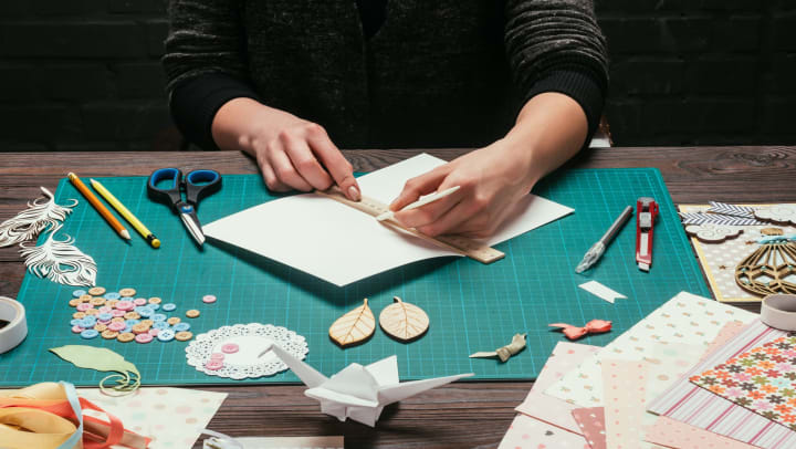 Person in front of a table with a ruler and pencil in their hands and scrapbooking supplies fanned out around them.