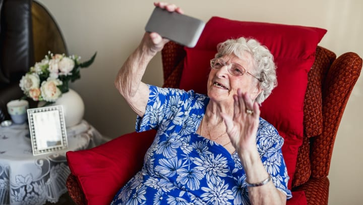 An elderly woman is using a smartphone