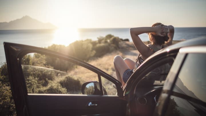 Resident relaxing on the hood of her car watching the sunset while on a road trip from her home at Sundance Creek in Midland, Texas