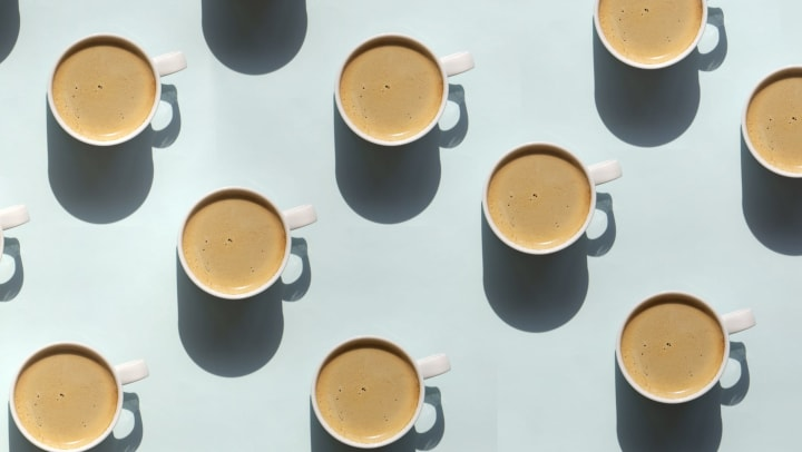 Pattern made of a cup of cappuccino on blue background.