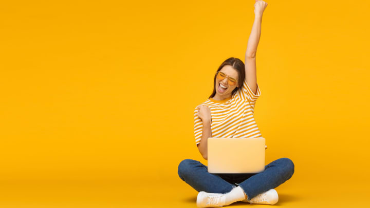 Smiling woman sitting on floor with laptop pumping fist