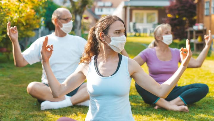 Multigenerational group of people doing yoga exercises outdoors while social distancing and wearing protective masks.