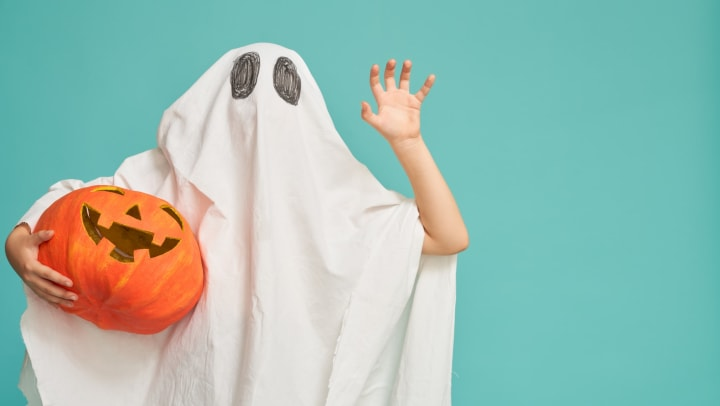 Child dressed as a ghost holding a pumpkin celebrating Halloween at Sedona Ranch