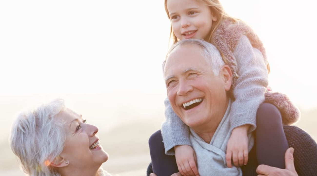 Happy resident couple and their granddaughter enjoying a day at the beach near Palo Alto Commons in Palo Alto, California
