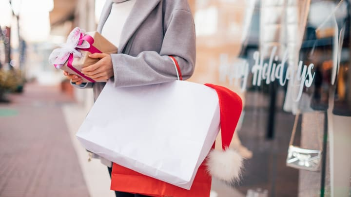 A girl holding a gift in her hands and shopping bag over her arm in front of a clothing store