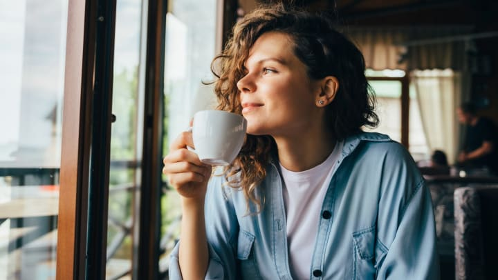 Woman smiling looking out the window drinking coffee