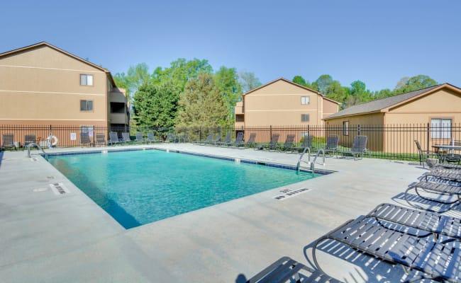 Poolside lounge chairs at Woodbrook Apartment Homes in Monroe, North Carolina