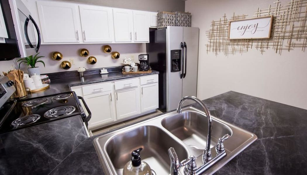 Modern kitchen with granite counters at Watercress Apartments in Maize, Kansas