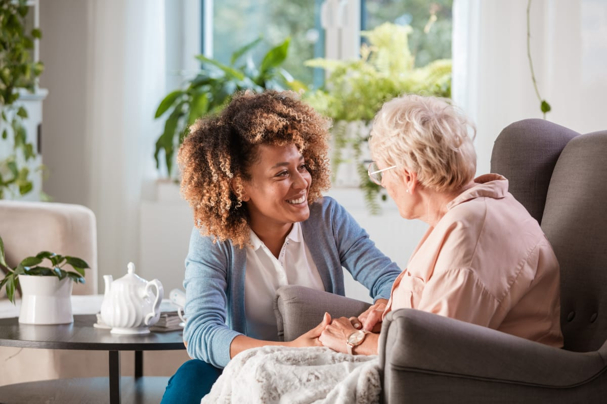 young caretaker talking to a resident at Cedar Crest Memory Care in Lafayette, Louisiana