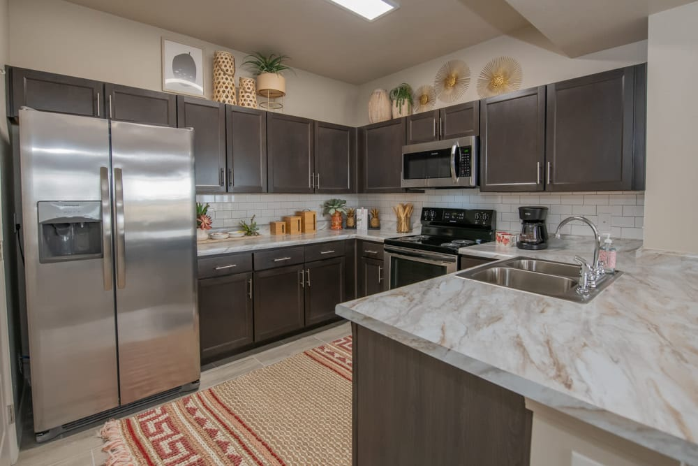 Modern kitchen with stainless-steel appliances in a model home at Redbud Ranch Apartments in Broken Arrow, Oklahoma