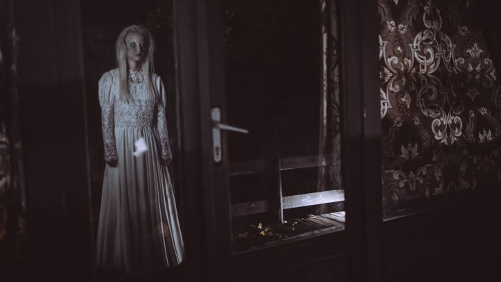 Scary woman standing behind a glass door in a haunted house near Cadia Crossing