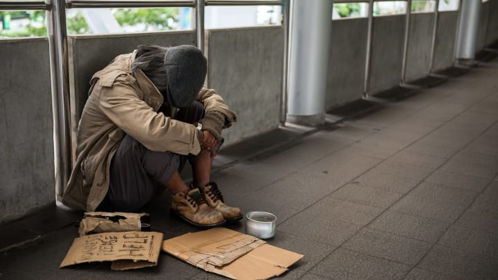 Homeless person seeking help from those nearby