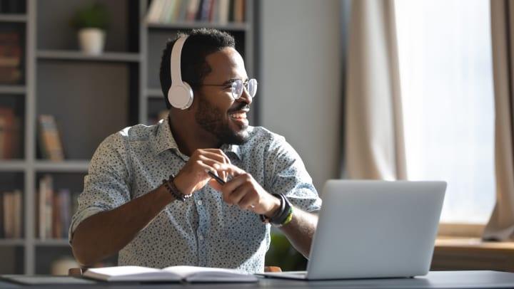 Man wearing headphones, sitting in home office