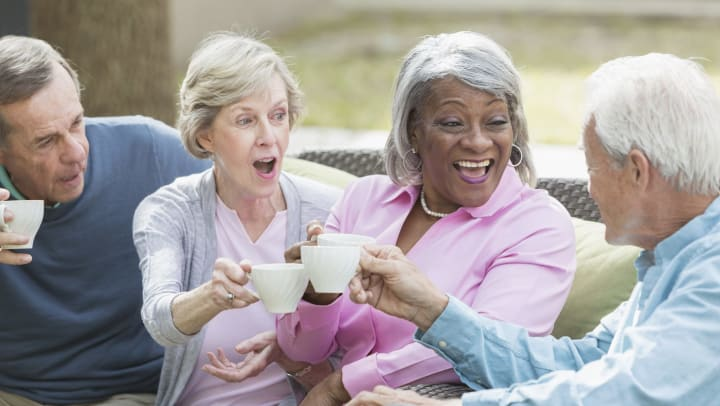Group of elderly people sitting near each other and toasting white coffee mugs.