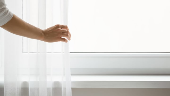 An adult hand is touching sheer curtains in front of a brightly lit window.