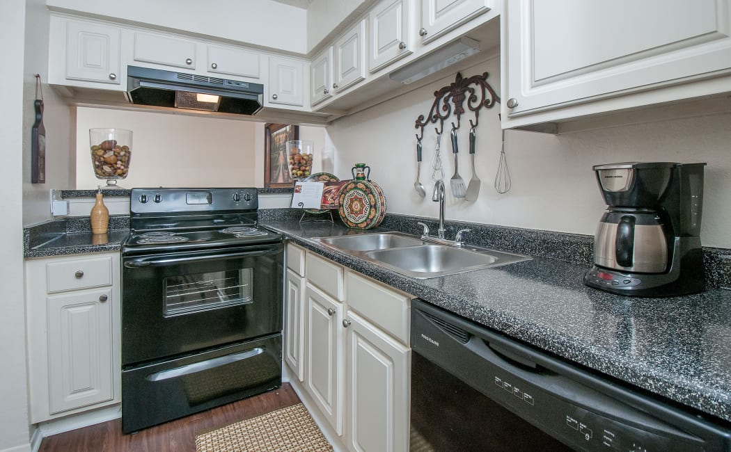 Gourmet kitchen white cabinetry and granite countertops in model home at Grayson Ridge in North Richland Hills, Texas