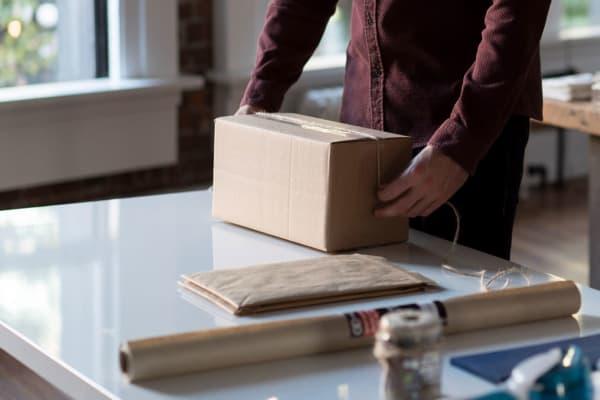 Person measuring a cardboard box