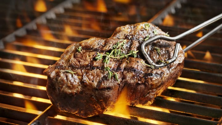 Juicy steak just finishing up on a barbecue grill at Olympus on Main in Carrollton, Texas