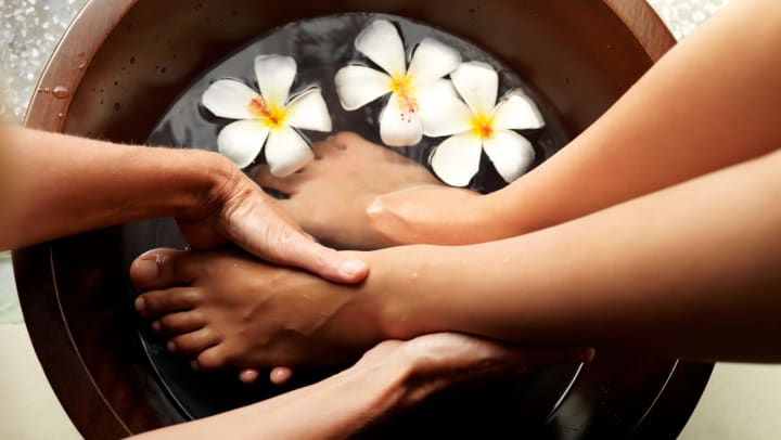 Female feet in a foot bath with floating tropical flowers, getting a pedicure.