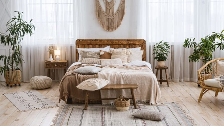 Elaborately made bed surrounded in throw rugs, wicker furniture, and plants.