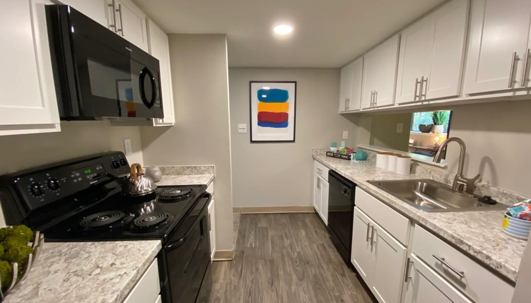 Modern kitchen with white cabinets in a model home at The Chimneys of Cradlerock Apartments in Columbia, Maryland
