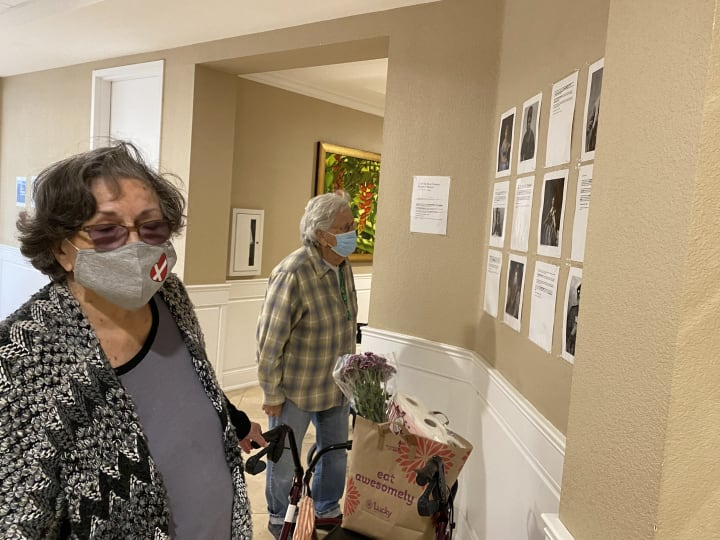 Residents at Gilroy read the historical women's bios posted on the walls of the community.