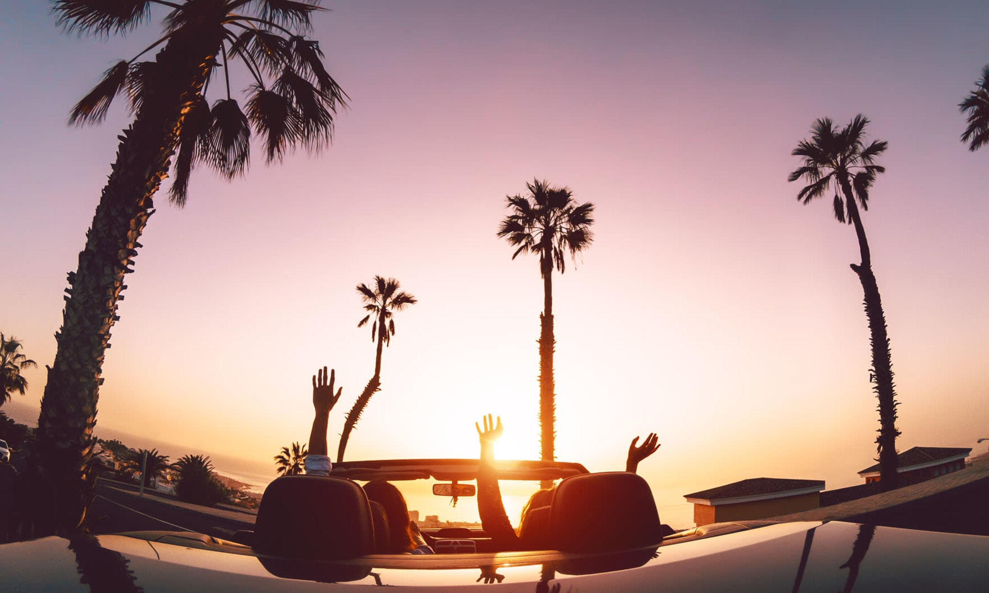Residents parked in a convertible at the beach raising their arms to the setting sun near Sendero Huntington Beach in Huntington Beach, California