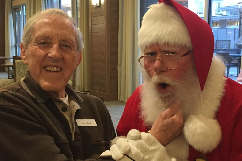 senior resident taking a picture with Santa Claus at Merrill Gardens at Burien in Burien, Washington