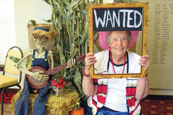 A resident holding a wanted sign at Estrella Estates Gracious Retirement Living in Goodyear, Arizona