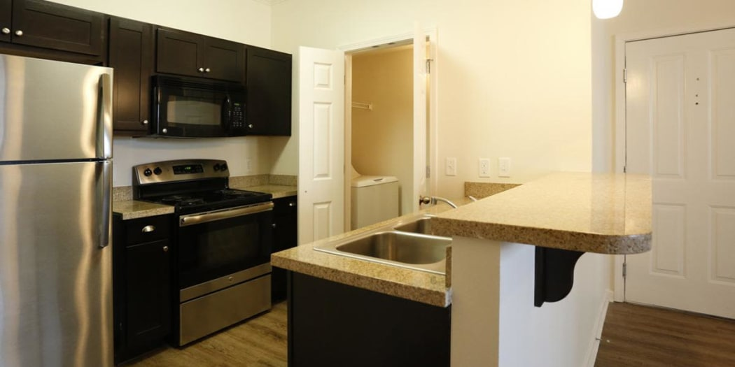 Modern kitchen with adjacent washer and dryer at Camden Lake Apartments in Baton Rouge, LA
