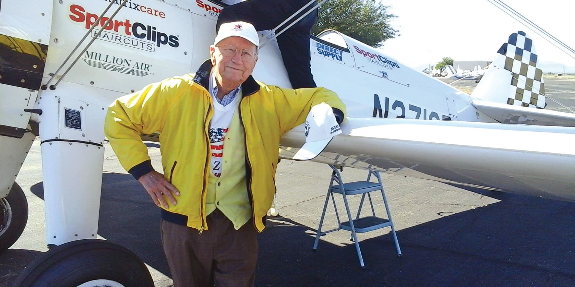 A resident from Fairview Estates Gracious Retirement Living in Hopkinton, Massachusetts posing next to a plane