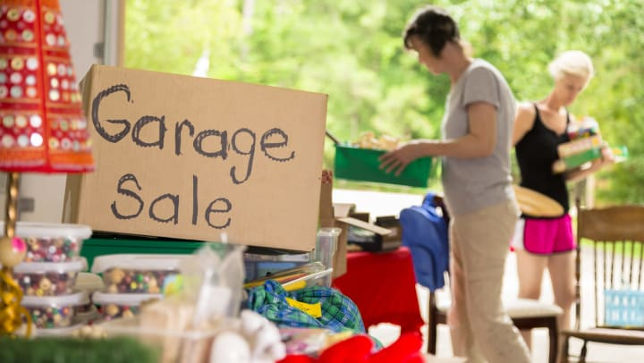 "Box with ""garage sale"" written on it, surrounded by knick-knacks, with two women in the background"