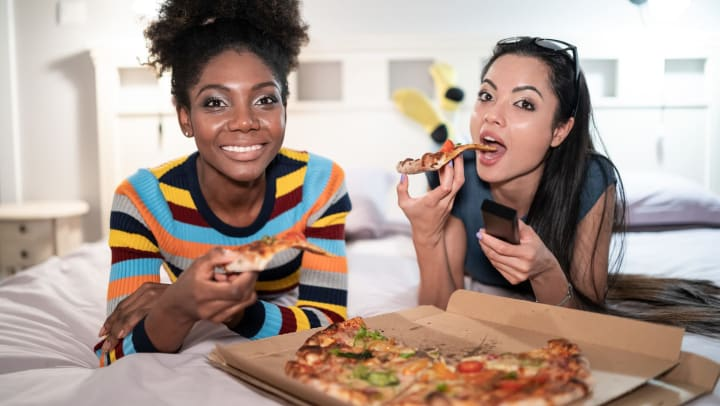 Resident friends enjoying some pizza in their new home at Olympus Sierra Pines in The Woodlands, Texas