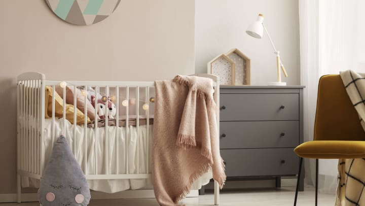 A room with a baby crib, dresser and chair.