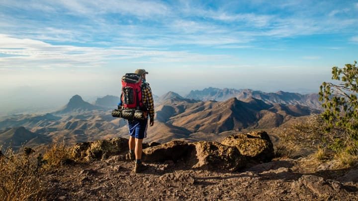 Person with a camping backpack on staring out at natural landscape.