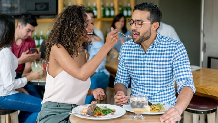 Woman feeding a bite of her food to a man with plates of food in front of them at a restaurant.