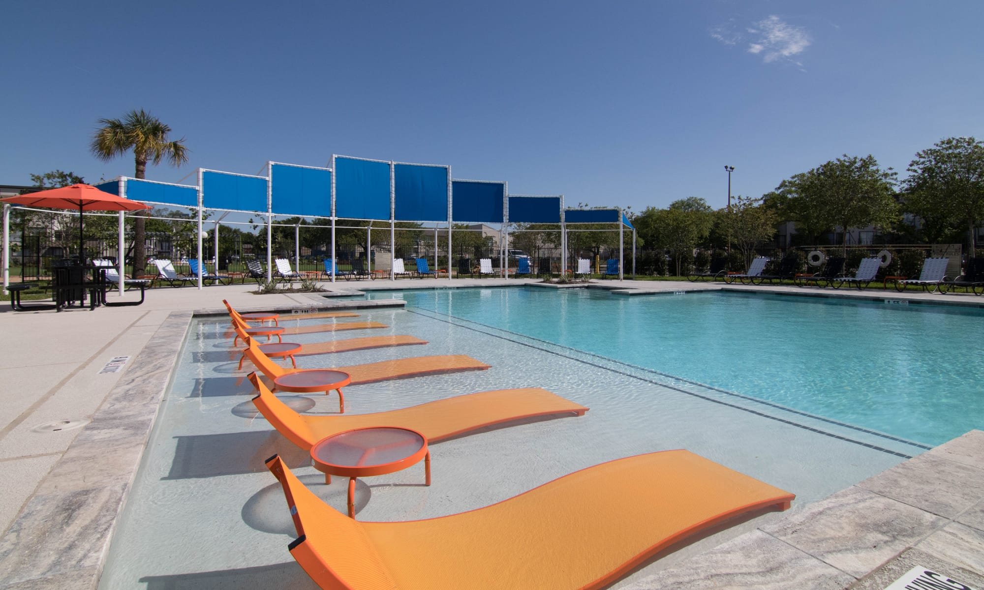 Beautiful swimming pool with tanning chairs at 2111 Holly Hall in Houston, Texas