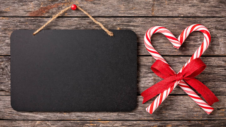 Blank chalkboard sign with candy canes tied with a ribbon in the shape of a heart.