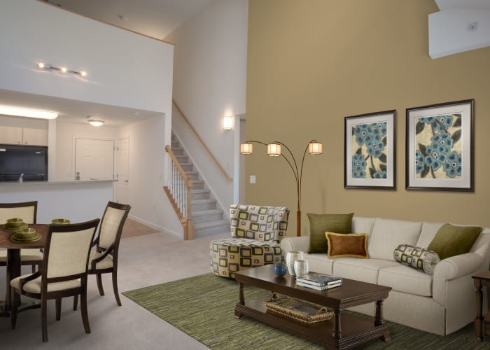 Well-decorated living room and dining area in model townhome at Prynne Hills in Canton, MA