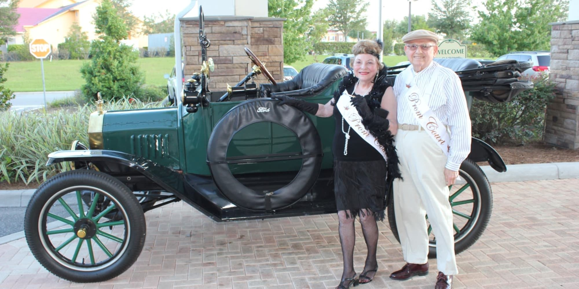 Two residents from Springwood Landing Gracious Retirement Living in Vancouver, Washington dressed for prom and posing in front of a car