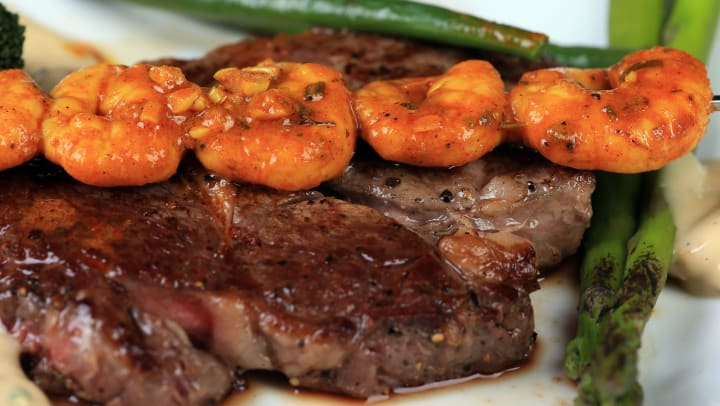 A well-done with steak with shrimp kabob on top.
