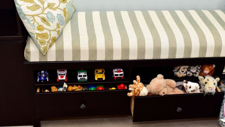 A wooden bench with a seating cushion in striped fabric has a shelf and drawers underneath for storage.