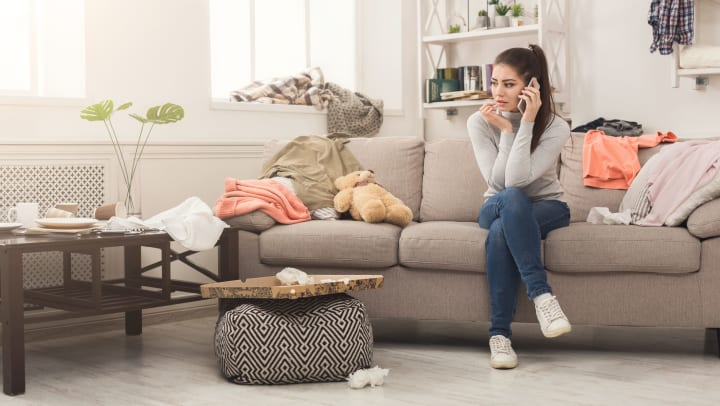A woman sitting on a sofa in a messy living room while talking on the phone.