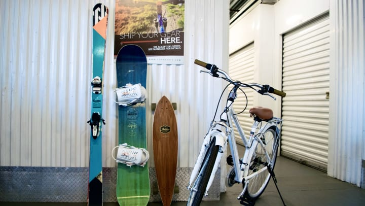 A pair of skis, a snowboard, a skateboard, and a bike in a storage facility hallway